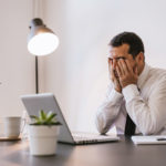Businessman under stress, fatigue and headache at the office